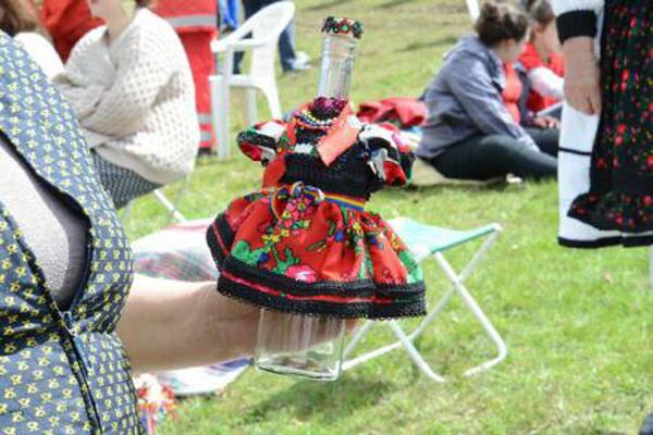 Palinca in bottles dressed in folk costume from Oas